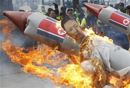Policemen watch as protesters burn an effigy of North Korean leader Kim Jong-Un bound on a mock missile during a protest against North Korea's rocket launch near the U.S. embassy in Seoul